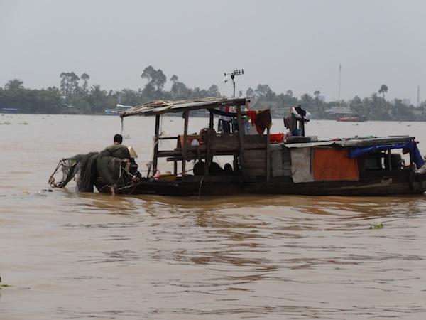 メコン川で沈みそうな船で生活している水上生活者